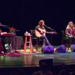 pam tillis country music star is accompanied by 2 younger musicians for stage performance