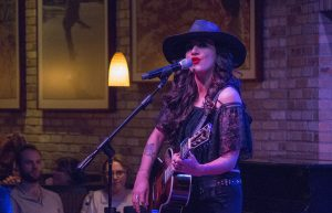 Singer-songwriter Lindi Ortega at the helm, near the microphone holding a guitar