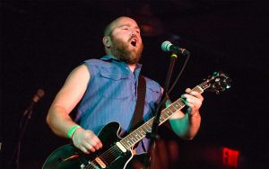 Lead singer Gabe Douglas singing into microphone while playing guitar