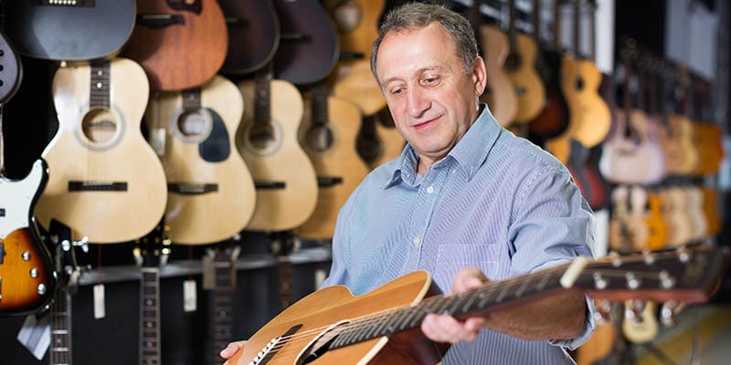older man holding acoustic guitar in store