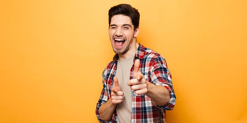 Man in plaid shirt in front of orange background smiling and winking