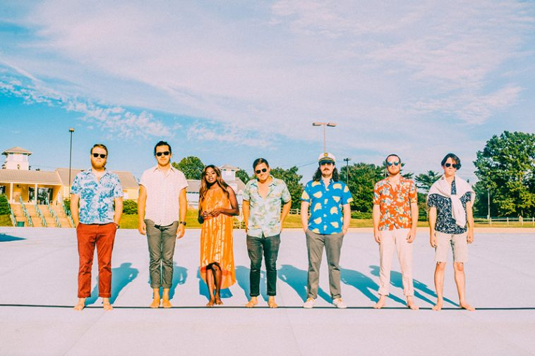 Music band LUTHI has seven members lined up in brilliant spring colors in a parking lot