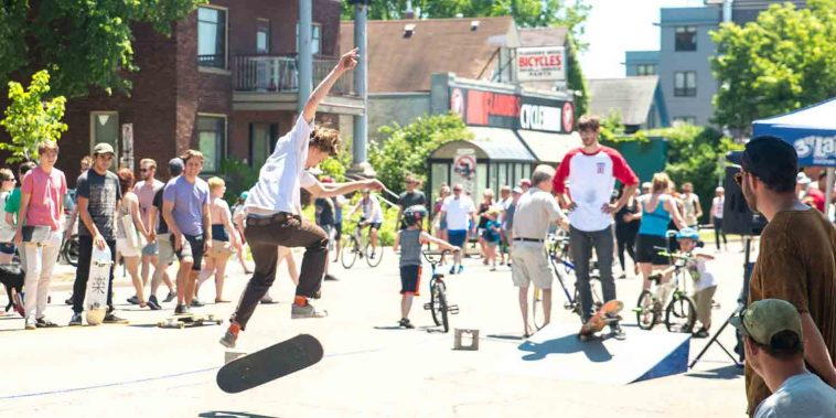 Skateboarders attempt tricks in middle of road