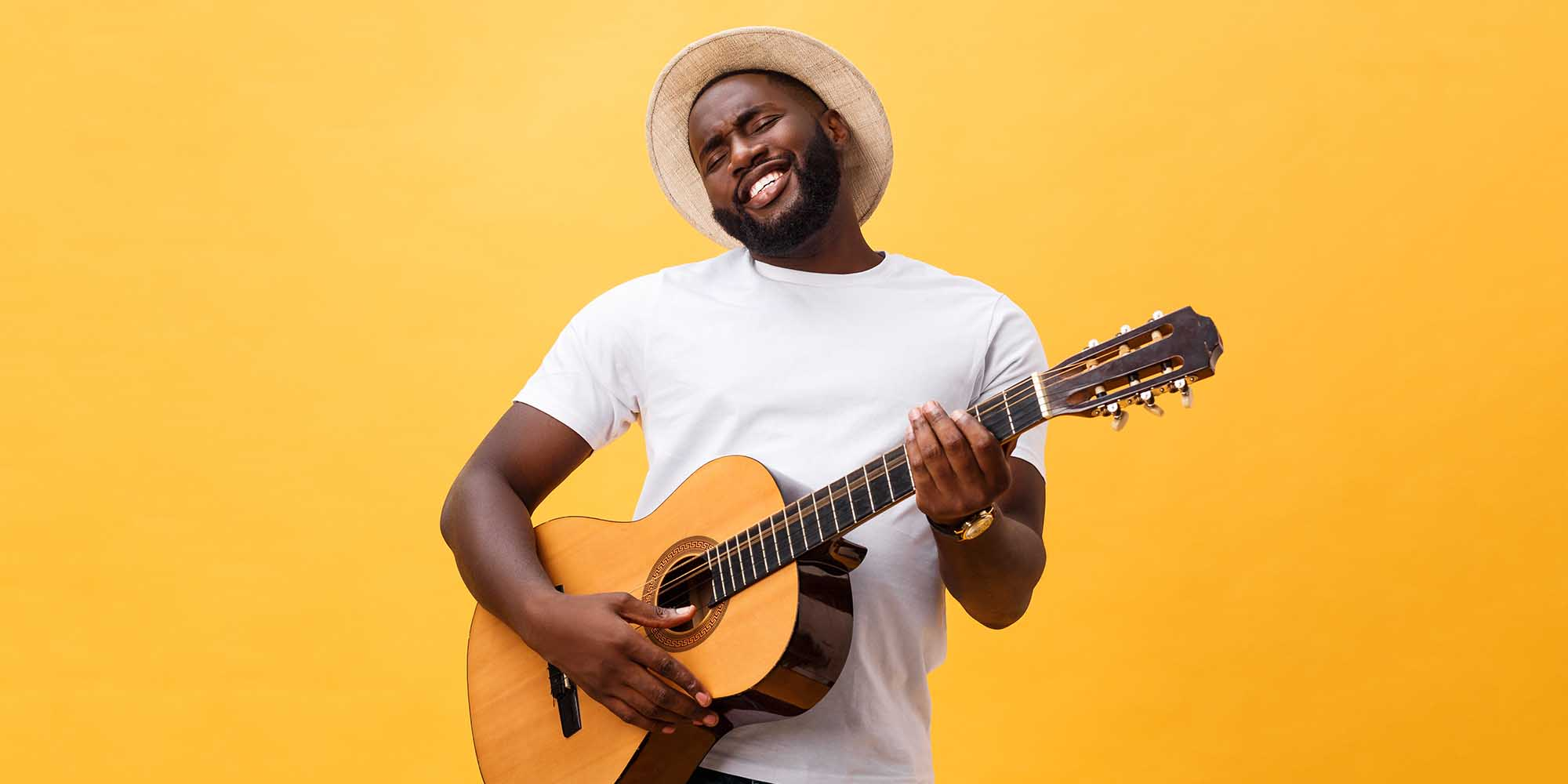 man playing acoustic classical guitar in from of yellow background wearing hat