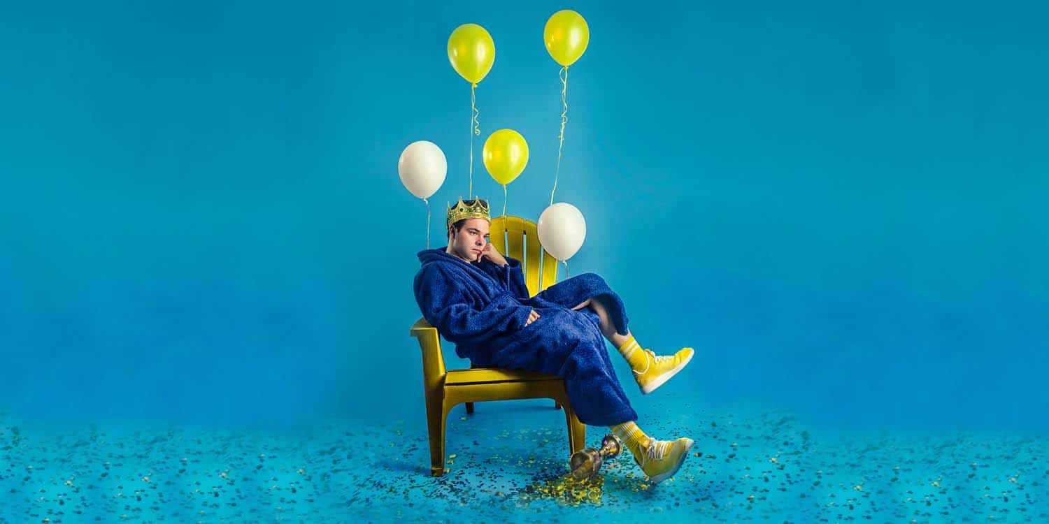 Grayson Dewolfe sitting on chair in blue robe and yellow balloons