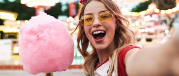 Girl with sunglasses at fair holding cotton candy