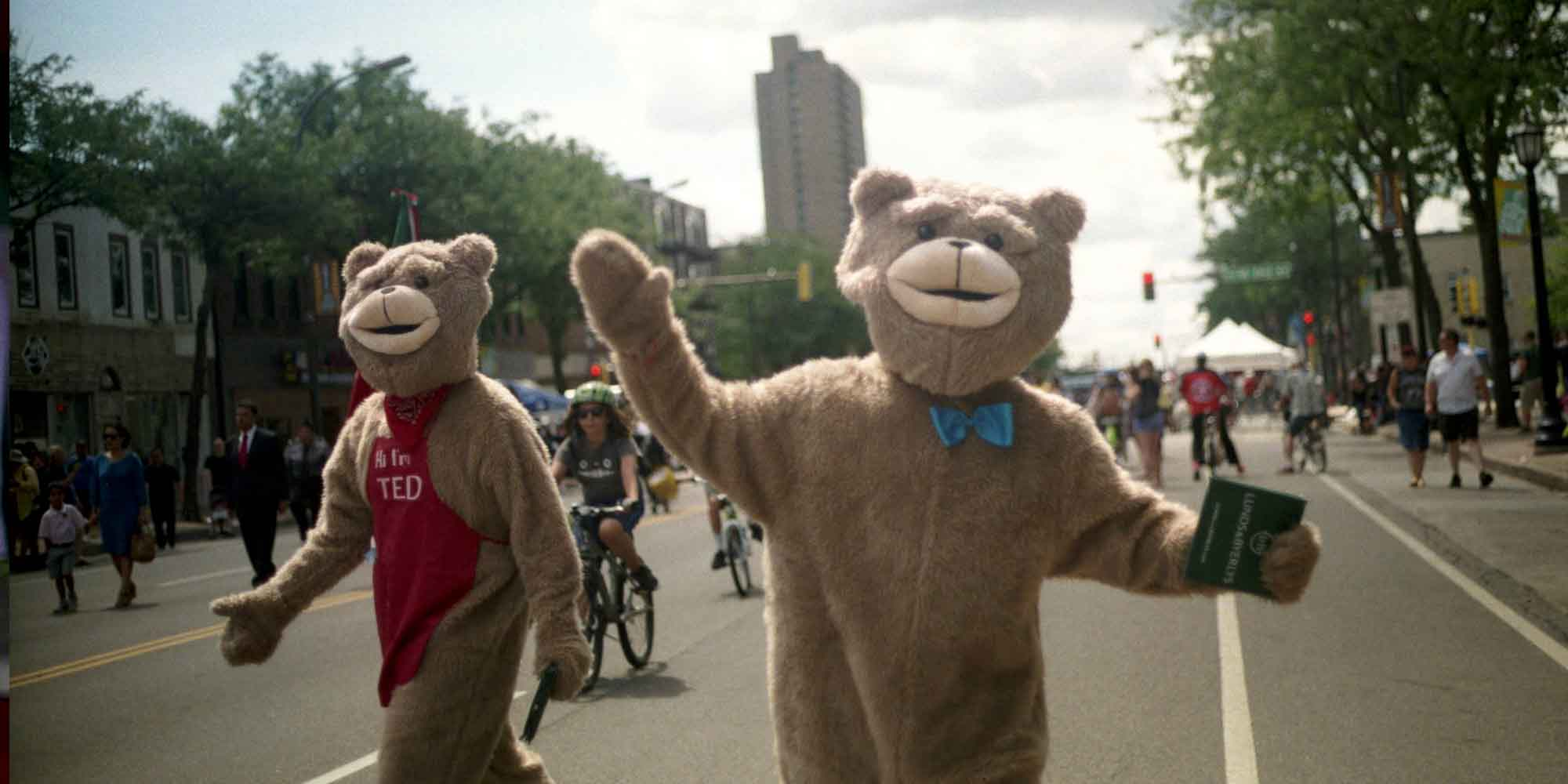 People in bear costume walking in road