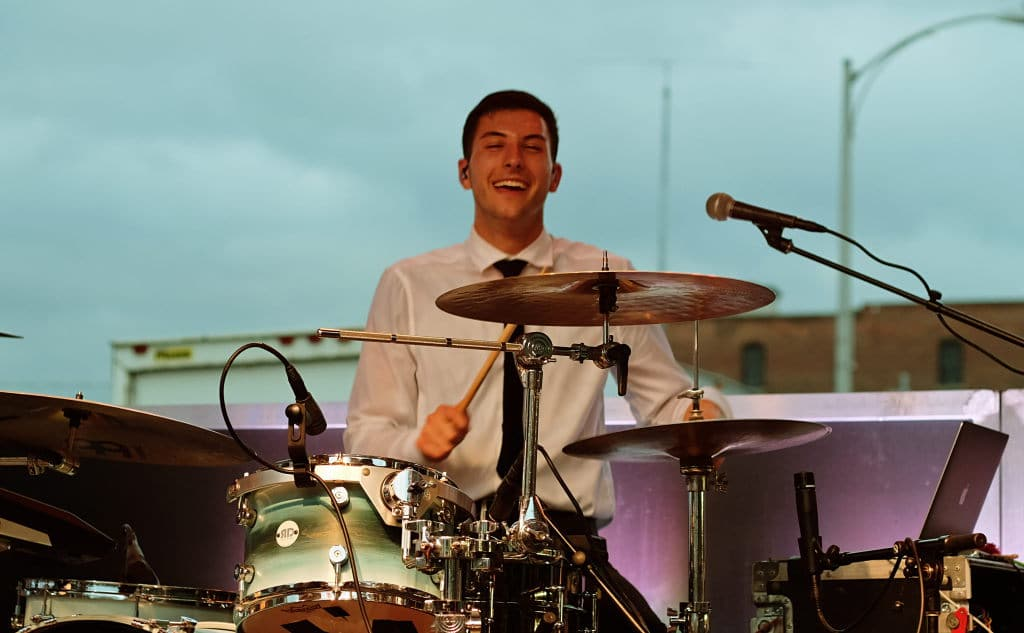 Yam Haus drummer grins on stage while playing