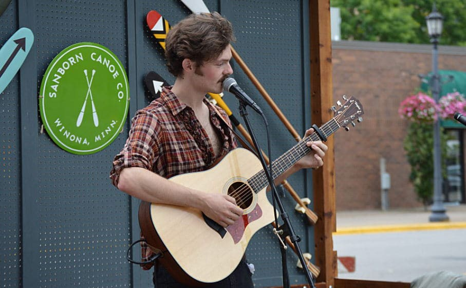 Josiah Smith plays guitar and sings into a microphone