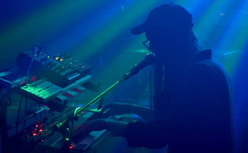 Dreamspook plays his synthesizer and sings into the microphone in a smoky venue