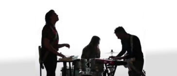silhouette of band members playing music in front of a white background