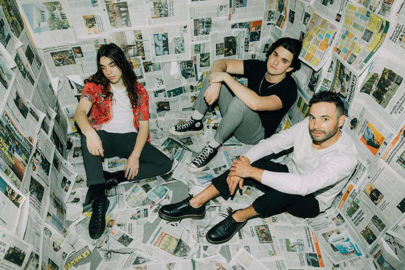 ufo ufo band photo. Three band members sitting in a room with newspaper on the walls