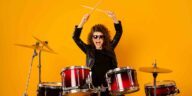 Girl drummer with sunglasses on and raising drum sticks